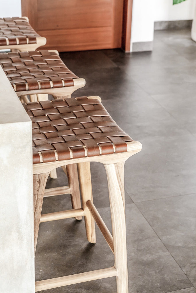 Three counter height Backless Woven Leather Counter dining stool at the kitchen counter. Handmade in Bali using Teak wood and vegetable-tanned leather imported from Java. - Saffron and Poe
