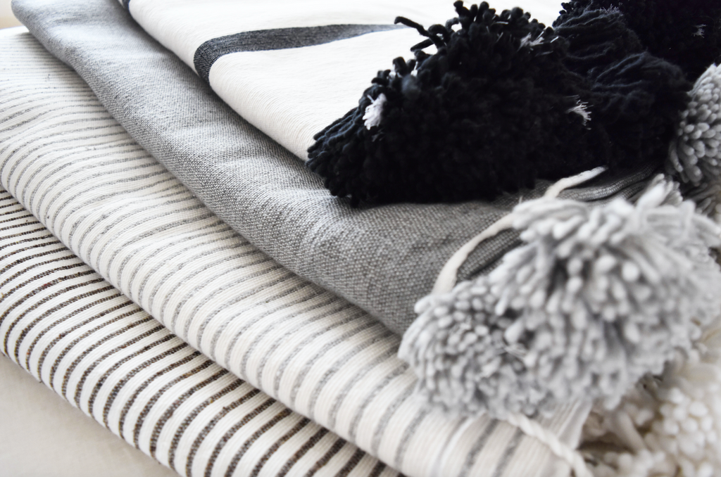 Three Bohemian blankets stacked and styled with Moroccan Pom Bed Throw - Dark Grey and White Stripes. Hand-woven in Marrakech using wooden looms. - Saffron and Poe