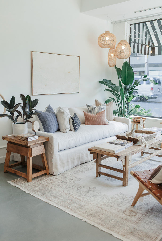 Styled antique chinese coffee table with vintage cedar side table on vintage rug with slipcovered sofa and assorted textile pillows and lumbars, with plants, books, and Kaleen Cameron art on white walls. - Saffron and Poe