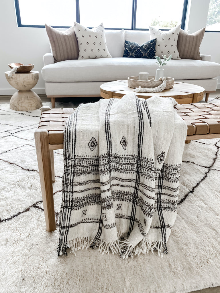 Draped handwoven indian bhujodi bed throw in natural over woven leather strap bench in beige in living room with natural oak and linen sofa, hemp textile pillows, antique Miao pillow, side tables, and moroccan area rug with windows in living room.