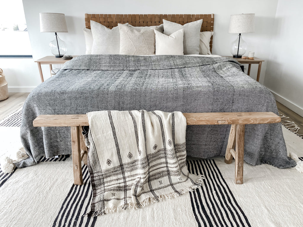 Styled bed with woven leather strap headboard in saddle, cream/neutral pillows, nightstands, moroccan area rug, antique vintage Chinese bench, uzumati bali moon candle, and draped handwoven Indian bhujodi bed throw in natural.