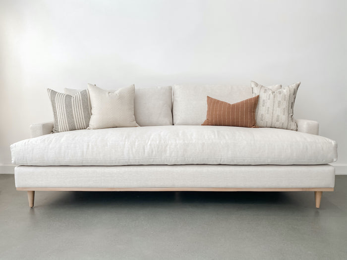 Front view of contemporary linen and oak sofa styled with Hmong textile pillows with white background and concrete floor.