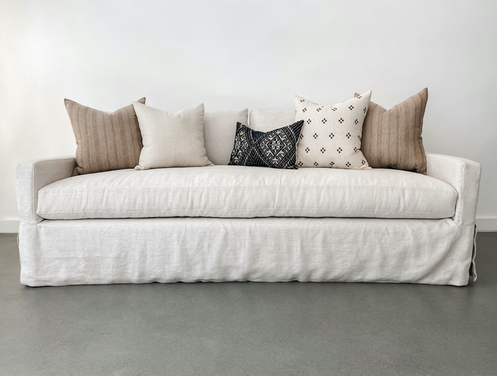 Shot of styled slipcovered sofa in natural linen fabric with assorted textile Hmong pillows against a white background and concrete floor.