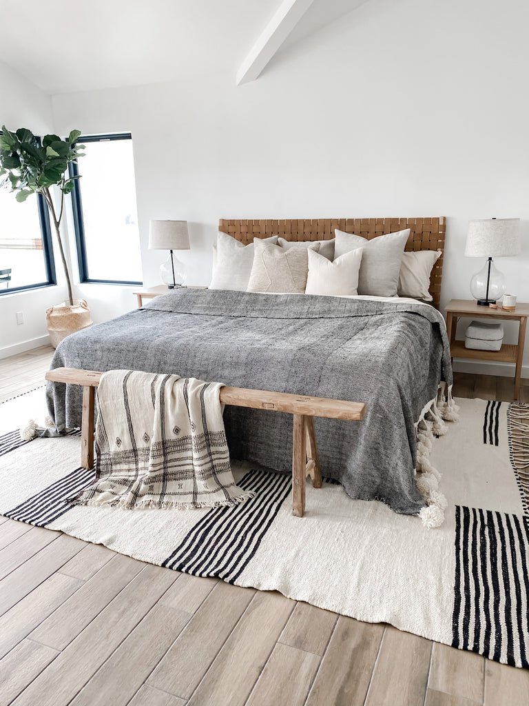 Styled in-situ angled shot of No. 14 Moroccan Kilimanjaros in bedroom with woven leather strap headboard in saddle, pillows, antique Chinese bench, handwoven Indian bhujodi bed throw, nightstands, woven bali beaded basket, and fiddle leaf fig tree on hardwood floors with white walls.