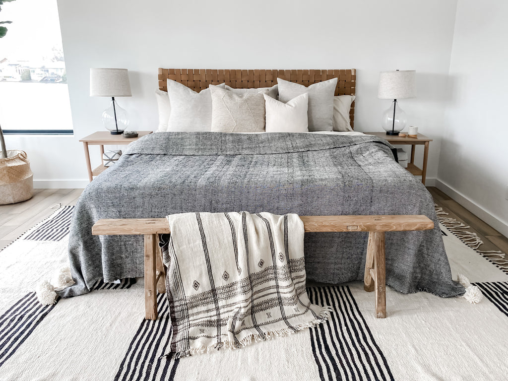 Styled front view of No. 14 Moroccan Rug in-situ with antique Chinese bench, handwoven Indian bhujodi bed throw, nightstands, pillows, woven leather strap headboard in saddle, nightstands, lamps, bali moon candle, and hardwood floors against white walls.