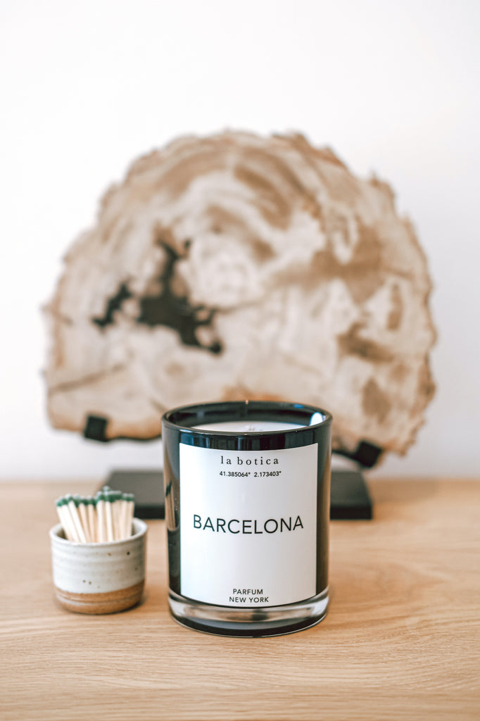 One La Botica Barcelona Candle set in front of Petrified Wood Sculpture and set next to Ceramic Matchstick holder with matches against a white background on a oak wood surface - Saffron and Poe