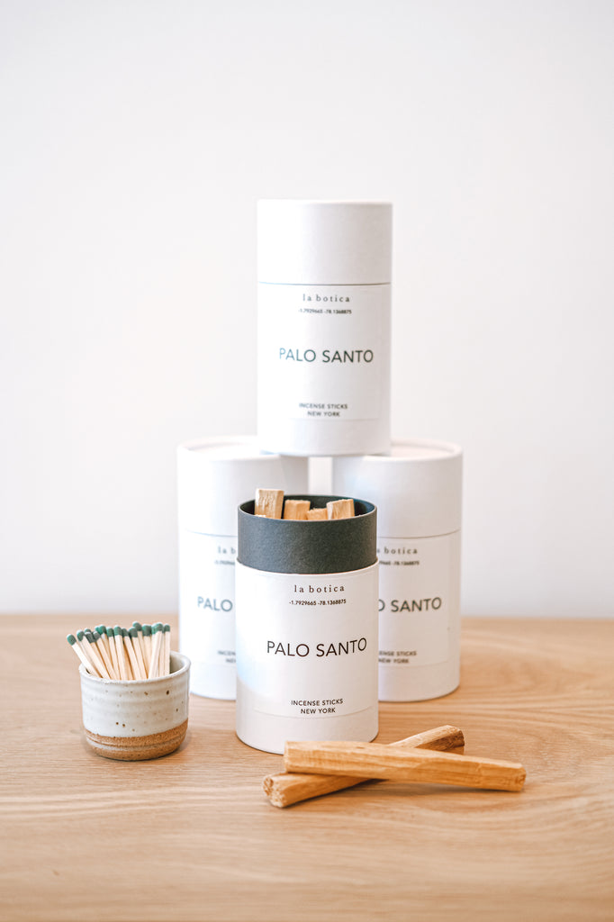 One La Botica Palo Santo Incense Sticks set in front of three stacked Palo Santo Incense Sticks with two incense sticks in front and a Ceramic Matchstriker set against a white background on an oak wood surface - Saffron and Poe