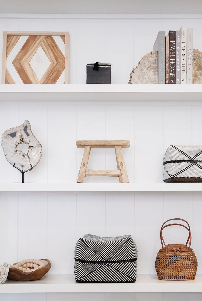 Styled petite rectangle stool on white shelf with hand beaded bali baskets, petrified wood bookends, tasseled bali beads, copper and teak bowl, ceramic canister, and Aleksandra Zee piece. - Saffron and Poe