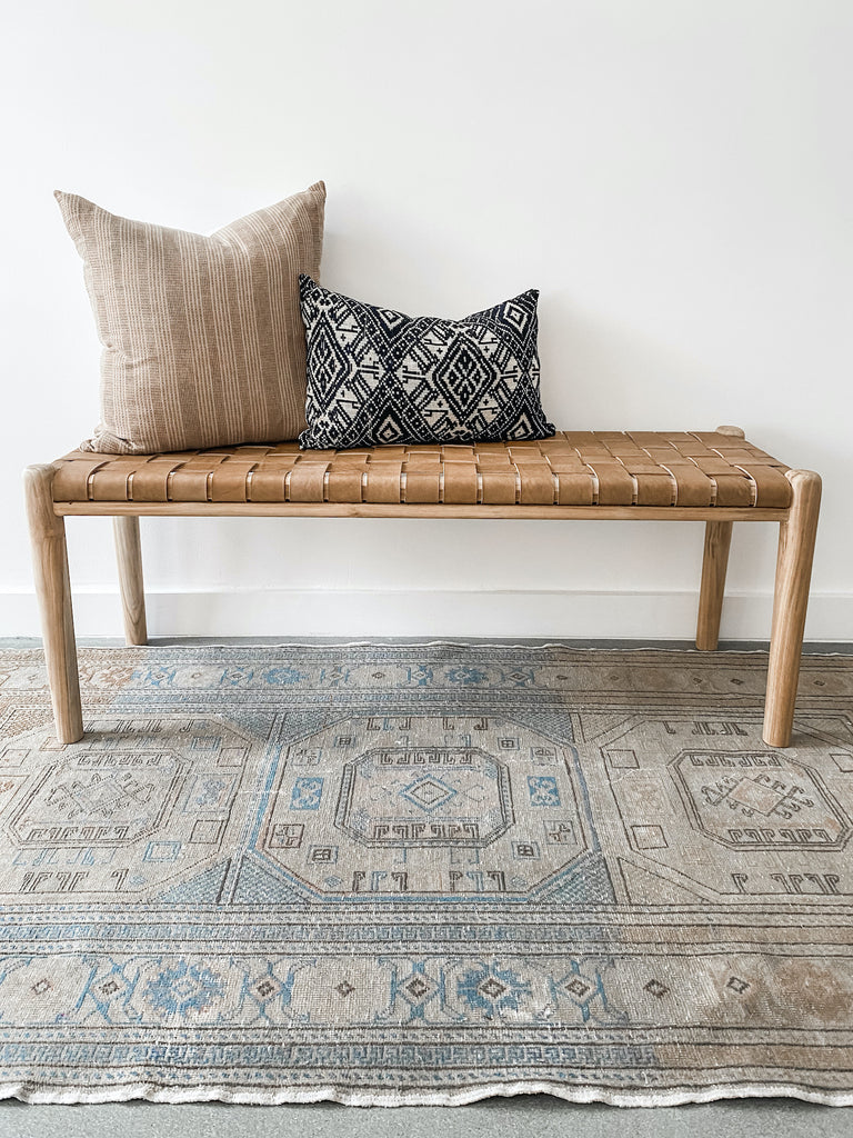 "Styled 48"" woven leather strap bench in beige with vintage Turkish oushak rug and two pillows. Handcrafted in Bali. - Saffron and Poe"