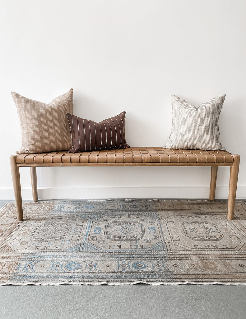 "Styled 60"" woven leather strap bench in beige with vintage Turkish oushak rug and three pillows. Handcrafted in Bali. - Saffron and Poe"