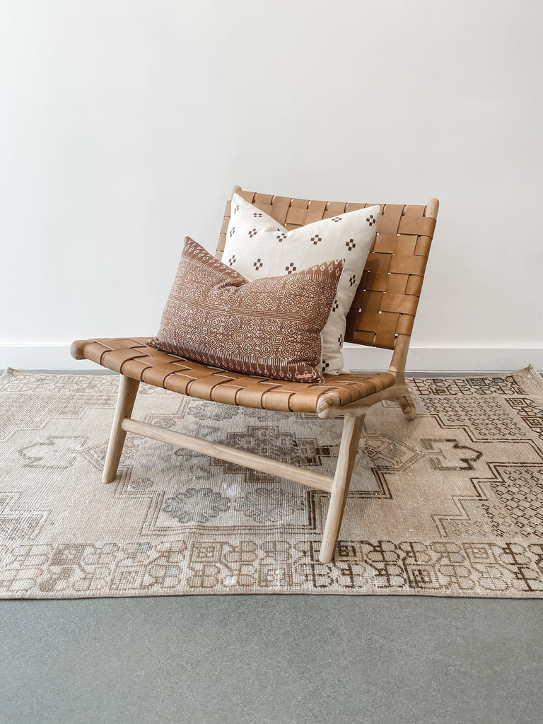 Styled view of Woven Leather Strap Lounge Chair in Beige against white background on vintage Turkish oushak rug with pillows. Teak wood and leather straps. Handcrafted in Bali. - Saffron and Poe