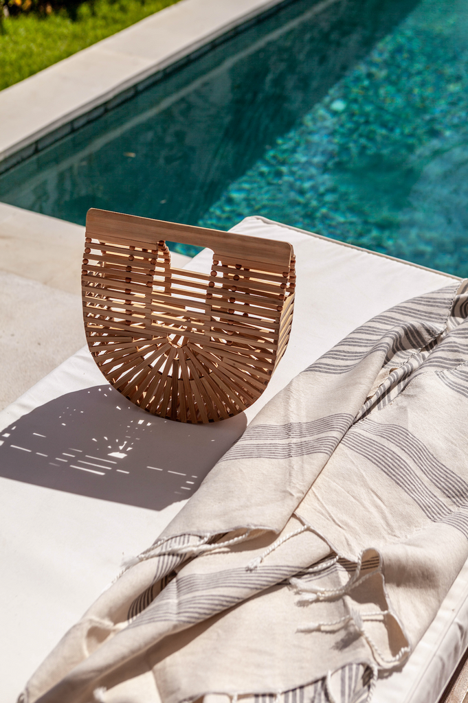 Bamboo Crescent Clutch boho bag styled at the pool with towel. Handcrafted in Bali with bamboo. - Saffron and Poe