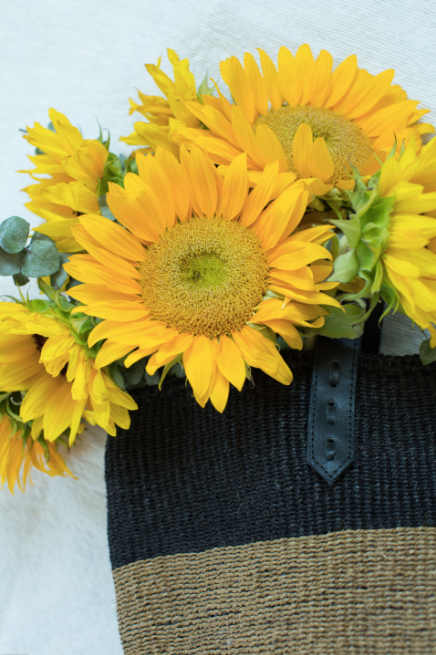 Woven Sisal Shopper bag up close with sunflowers. Handwoven in Kenya with sisal fiber and leather. - Saffron and Poe
