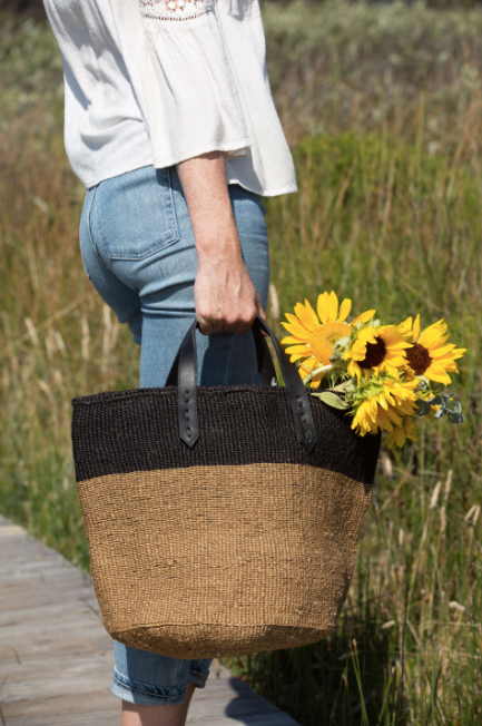 Woven Sisal Shopper bag in model hand with sunflowers. Handwoven in Kenya with sisal fiber and leather. - Saffron and Poe