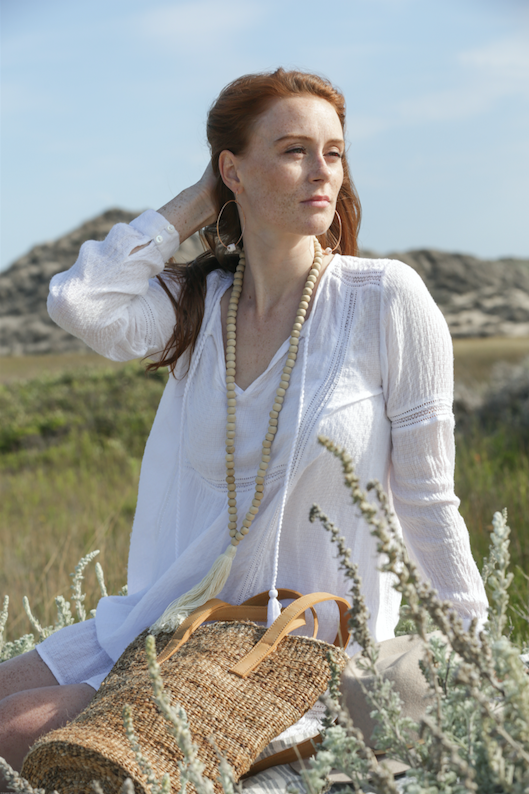 Model wearing Cream Tasseled Wooden Teak Bali Beads at the beach. Great for a necklace or an accessory handcrafted in Bali. -Saffron and Poe