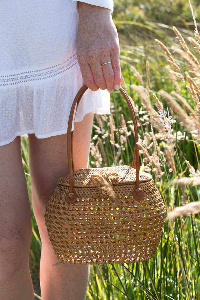 The model holding Tenganan Basket clasp Handbag. Small, chic, and Handmade in Tenganan, Bali using natural Ata reed. - Saffron and Poe