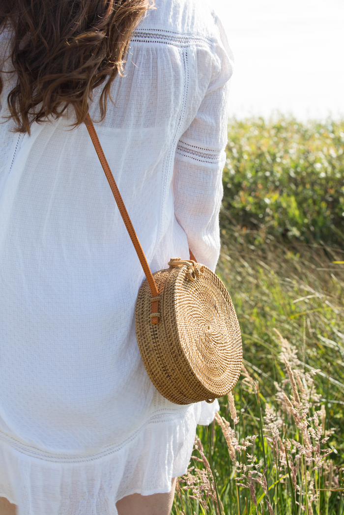 Beachy model look with casual, chic Tenganan Basket Crossbody Bag Round. Handmade in Tenganan, Bali using natural Ata reed and leather.  - Saffron and Poe