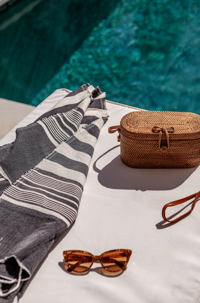 Styled laydown photo next to the pool with our Tenganan Basket Crossbody Bag - oval, small and chic. Handmade in Tenganan, Bali using natural Ata reed. - Saffron and Poe