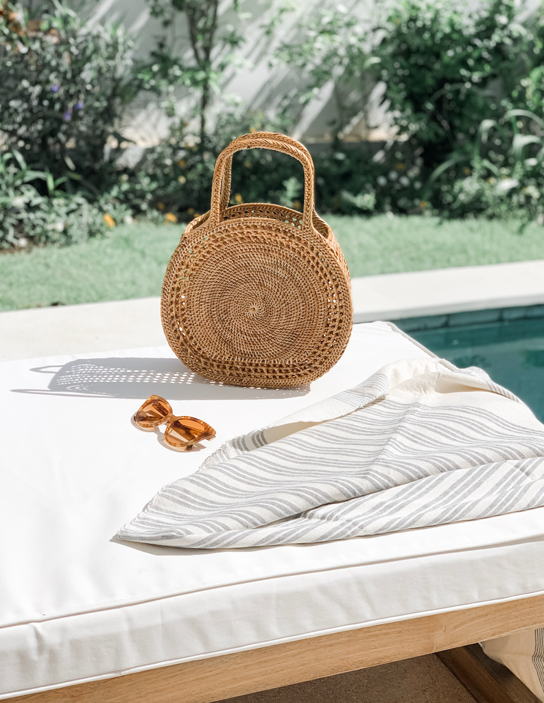 Styled pool flatlay with our Tenganan Basket Handbag, towel and sunglasses. Handmade in Bali with Ata reed - Saffron and Poe