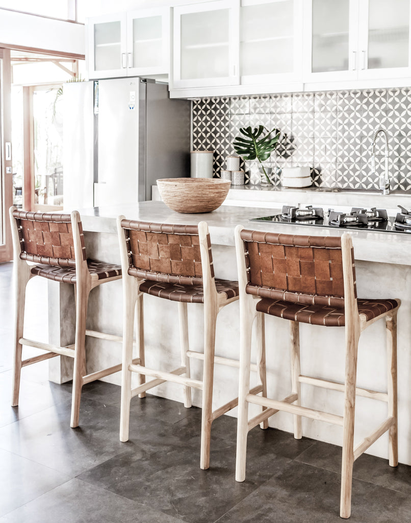 Three Woven Leather Strap Counter Stools in Saddle styled at open kitchen counter. Handcrafted in Bali using teak wood and leather. - Saffron and Poe