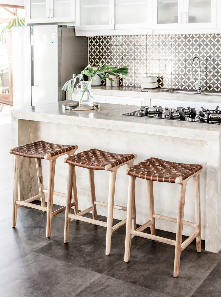 Open white kitchen styled with three counter height Backless Woven Leather Counter dining stools. Handmade in Bali using Teak wood and vegetable-tanned leather imported from Java. - Saffron and Poe