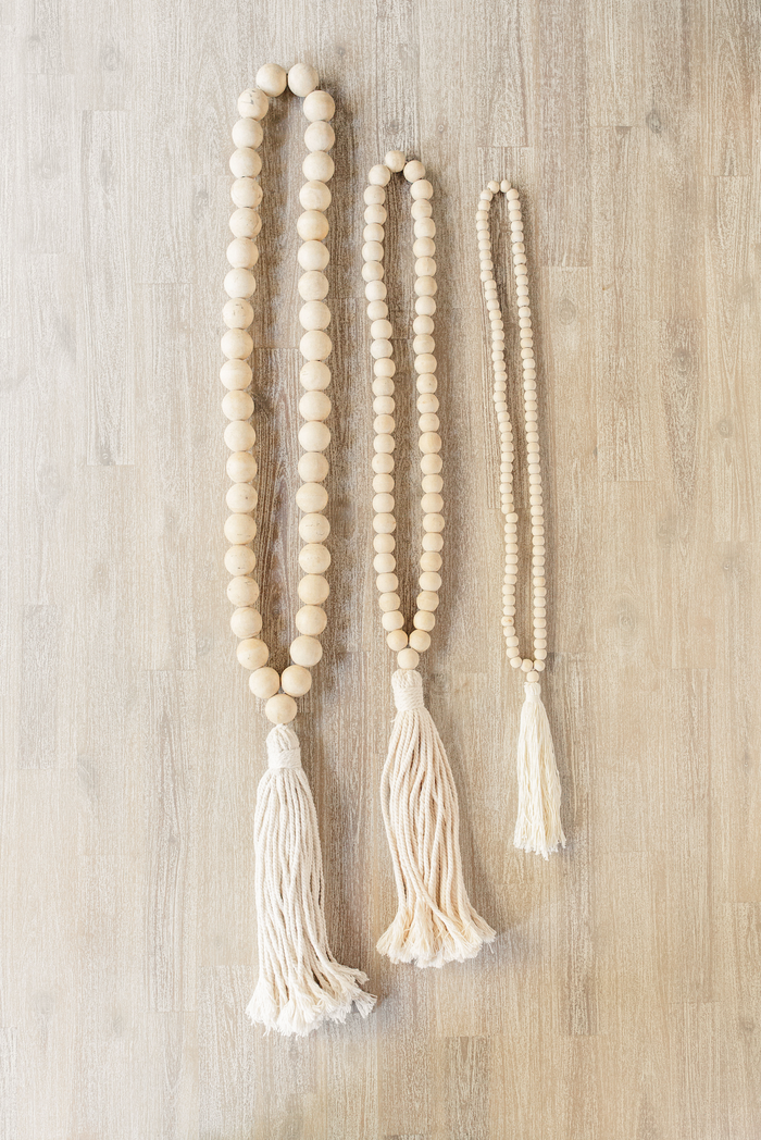Three strings of Cream Tasseled Wooden Teak Bali Beads layed down. Great for a necklace or an accessory handcrafted in Bali. -Saffron and Poe