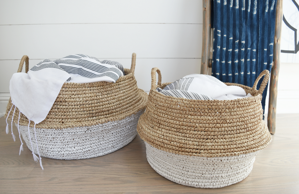 Two collapsible woven Hyacinth Storage Accent Baskets styled in livingroom with blankets inside. Handmade in Bali using natural and white painted water hyacinth. - Saffron and Poe