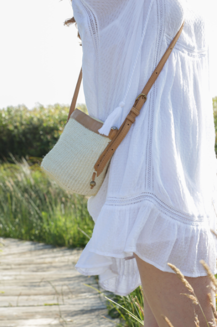 Bohemian style Woven Sisal and Leather Handbag crossbody in cream on model at beach white dress. Bag Handwoven in Kenya. - Saffron and Poe