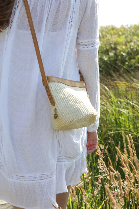 Bohemian style Woven Sisal and Leather Handbag crossbody in cream on model at beach. Bag Handwoven in Kenya. - Saffron and Poe
