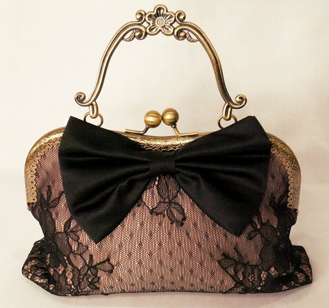 Black lace over blush satin handbag with black bow and antique brass frame with handle