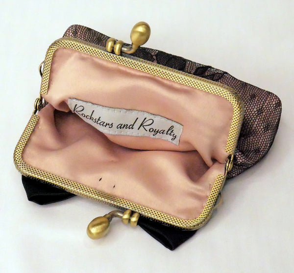 Small purse made of blush satin with a black lace overlay, black satin bow and antique brass frame.