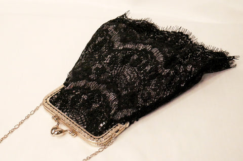silver sequin pouch bag with black lace overlay, silver frame, and silver chain wrist strap