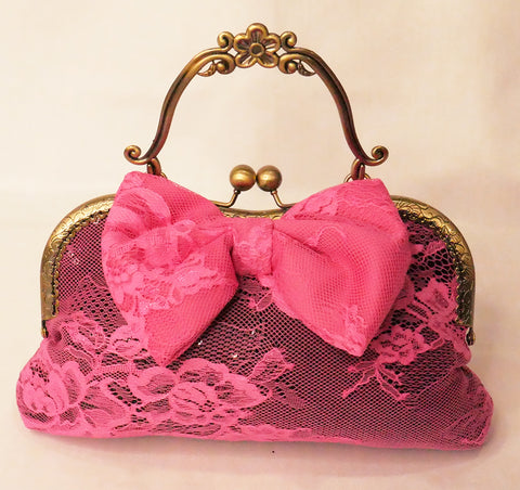 black sequin handbag with a pink lace overlay and pink bow, attached to an antique brass frame with a handle