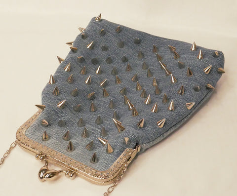 Blue denim handbag with silver studs and a silver star patch, with pink satin lining and a silver metal frame and chain wrist strap