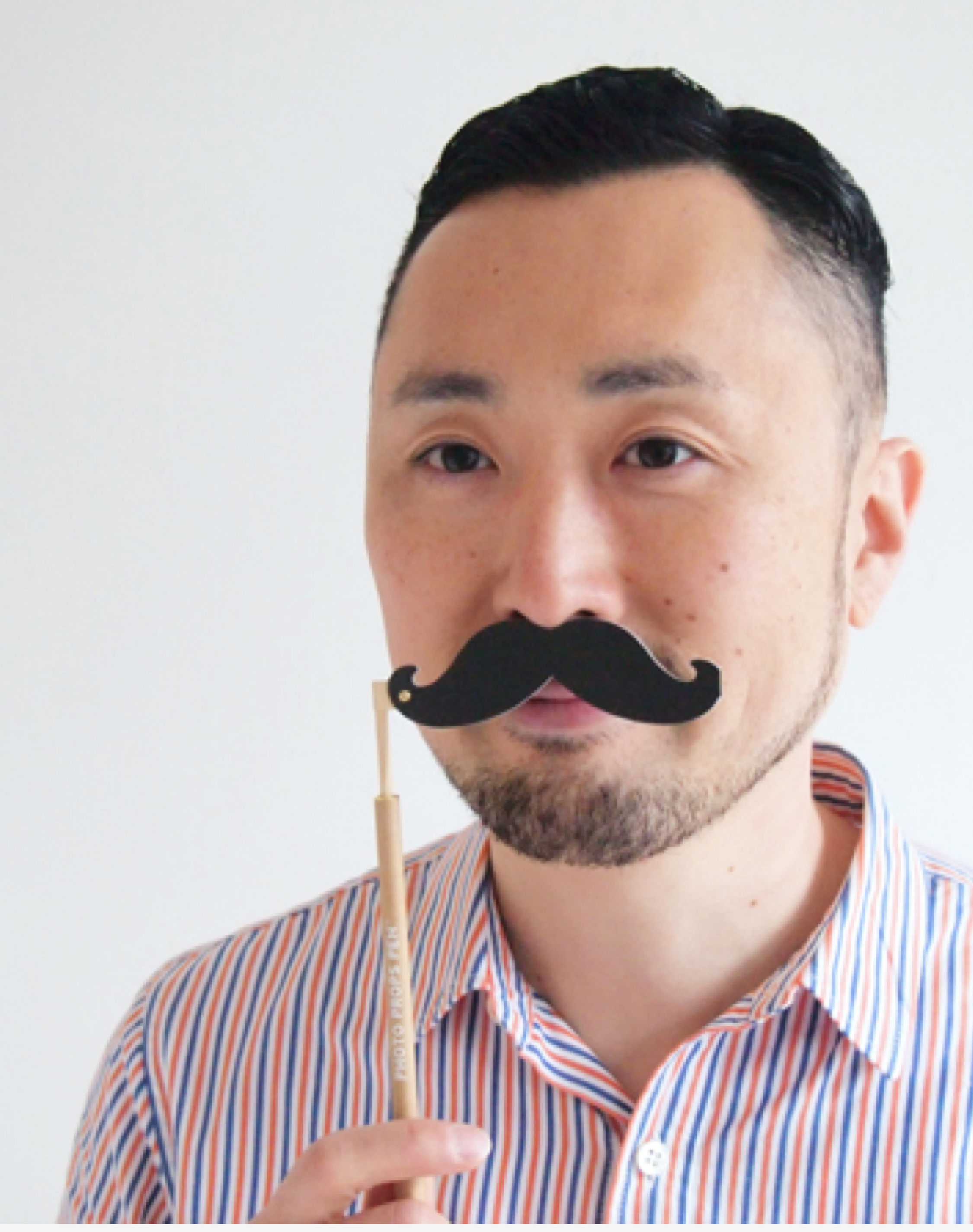 A man is trying a mustache photo props pen