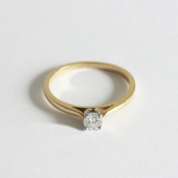 a classic diamond solitaire engagement ring in yellow and white gold