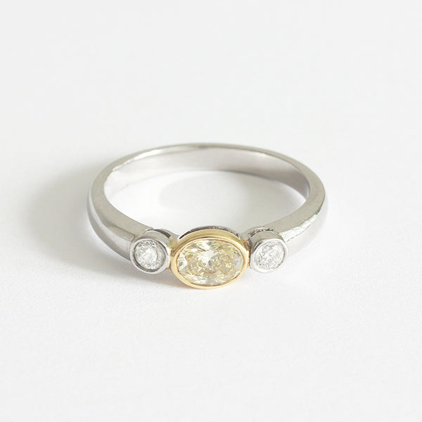 a platinum rub over set 3 stone ring with one oval central natural yellow diamond and 1 white diamond each side