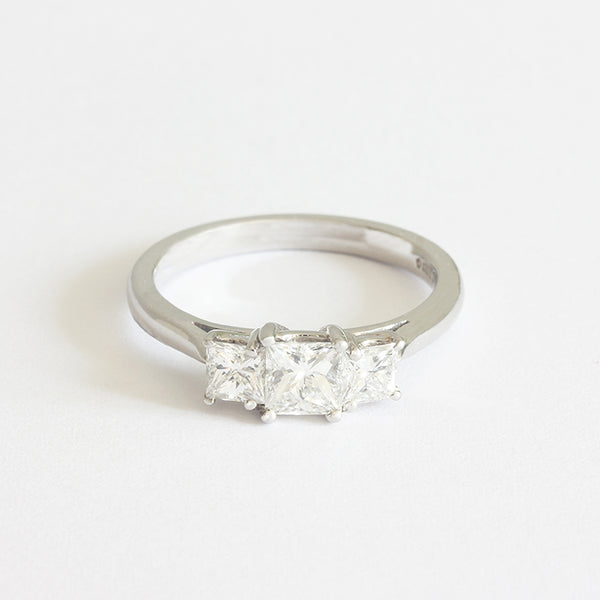 a 3 stone diamond engagement ring with 3 princess cut diamonds and set in platinum