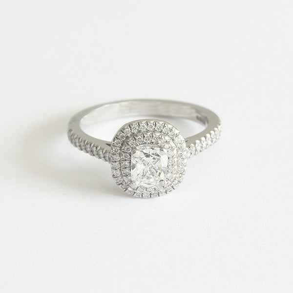 a claw set diamond target cluster ring in platinum diamond shoulders