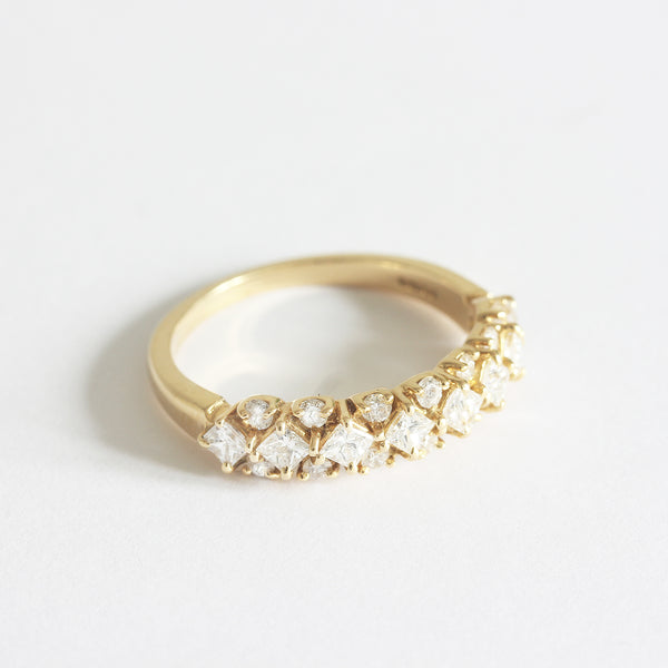 a yellow gold diamond set ring with square stones and round stones