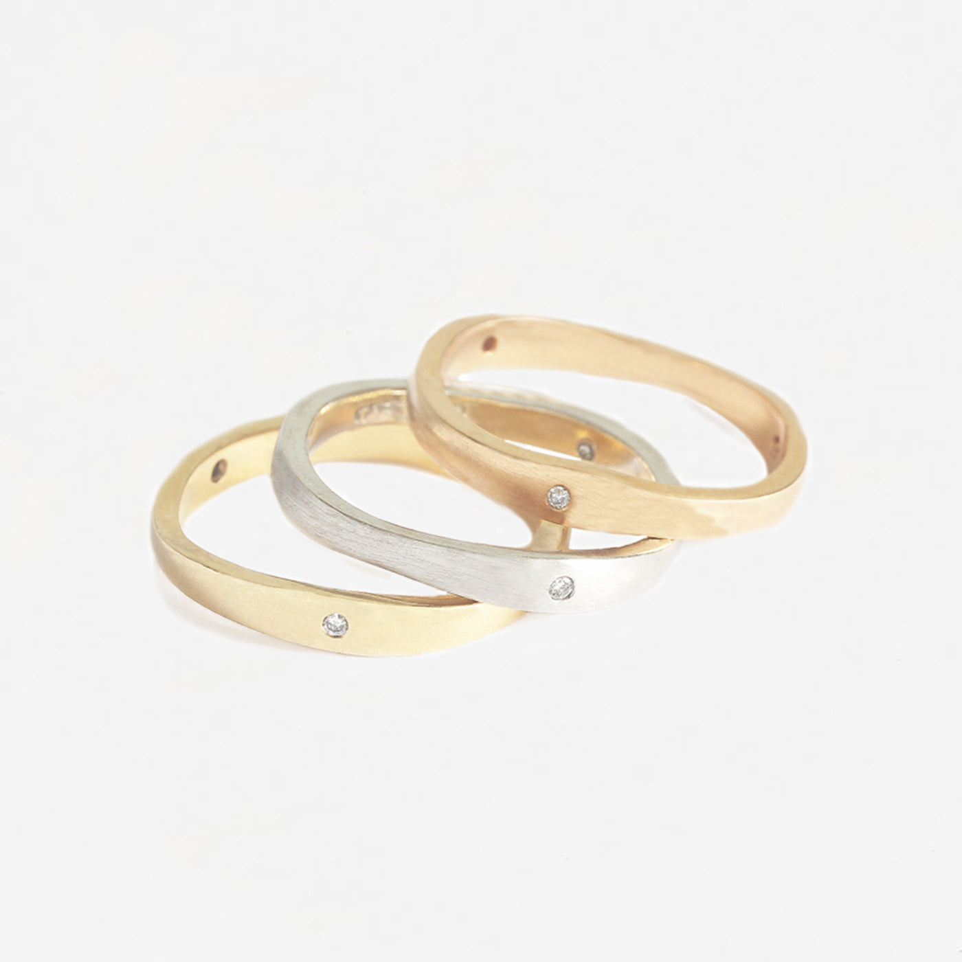 a beautiful set of 3 rings in rose yellow and white gold with a matte finish and diamonds