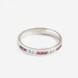 a pink sapphire and diamond half eternity ring in white gold