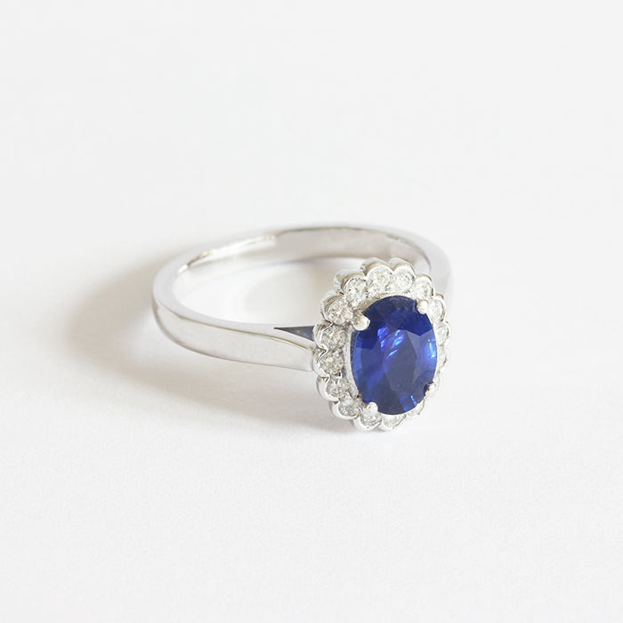 a beautiful oval sapphire and diamond set cluster ring in white gold