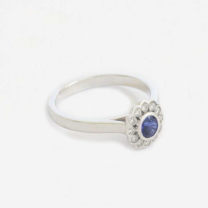 a white gold modern sapphire and diamond round cluster ring in rub over setting