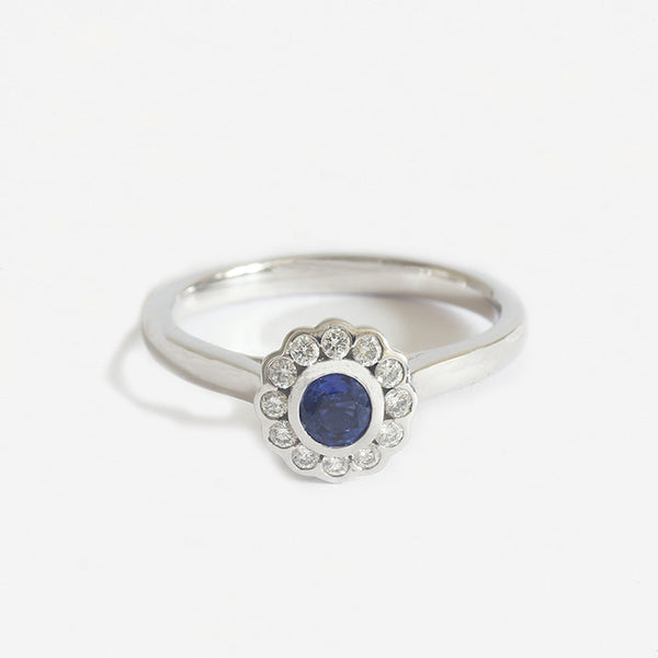 a sapphire diamond round cluster ring in white gold rub over set