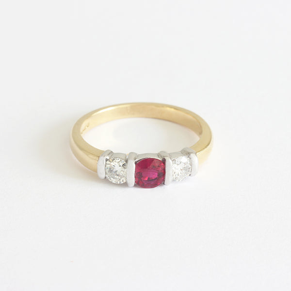 a gold 3 stone ring with one ruby and 2 diamonds
