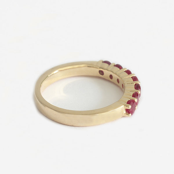 a yellow gold ruby half eternity ring with 7 round stones and claw set