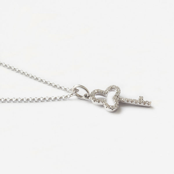 a white gold diamond set key shaped pendant and chain