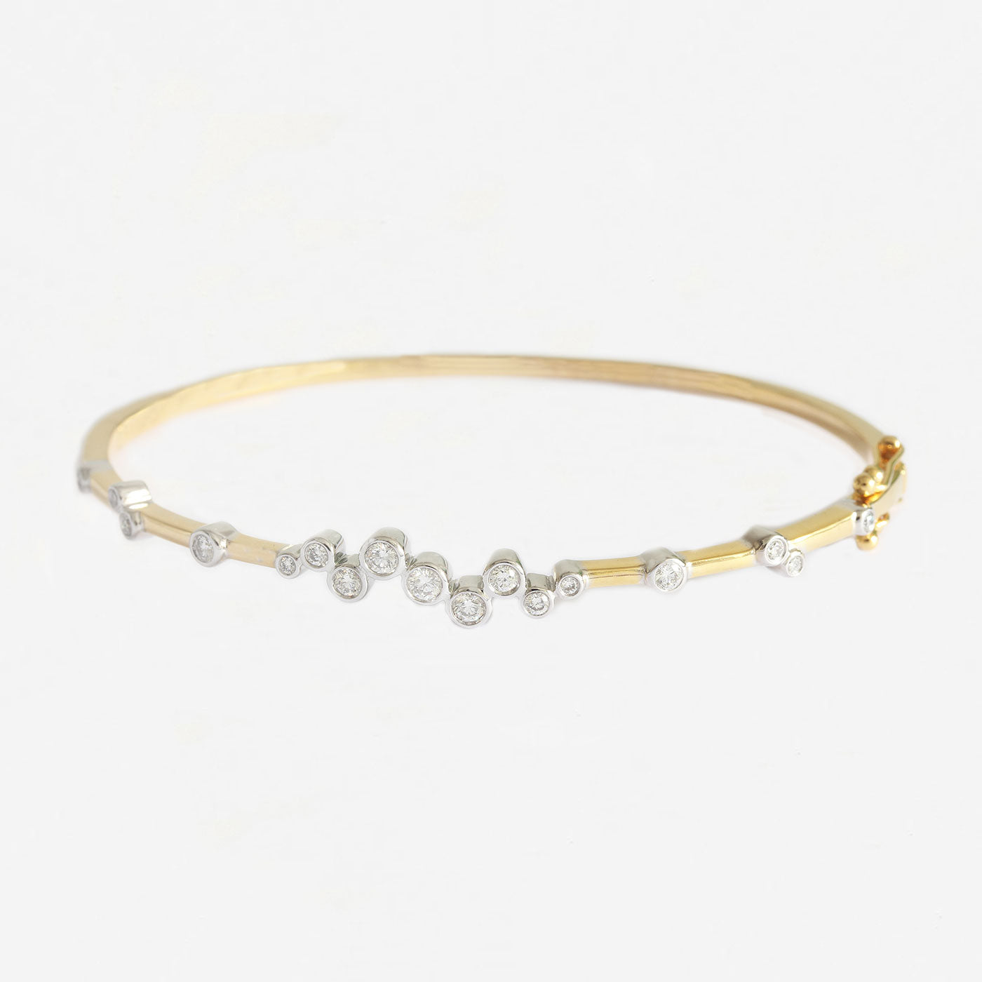 a contemporary diamond white and yellow gold hinged oval bangle