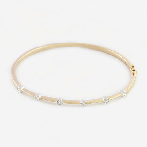 a modern yellow and white gold bangle with 6 round diamonds in a rub over set and oval shaped bangle with hinge